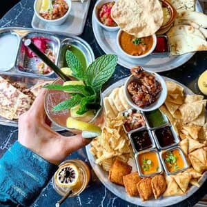 Indian Fast Casual Restaurant Hand holding drink and platters of food at franchisee location