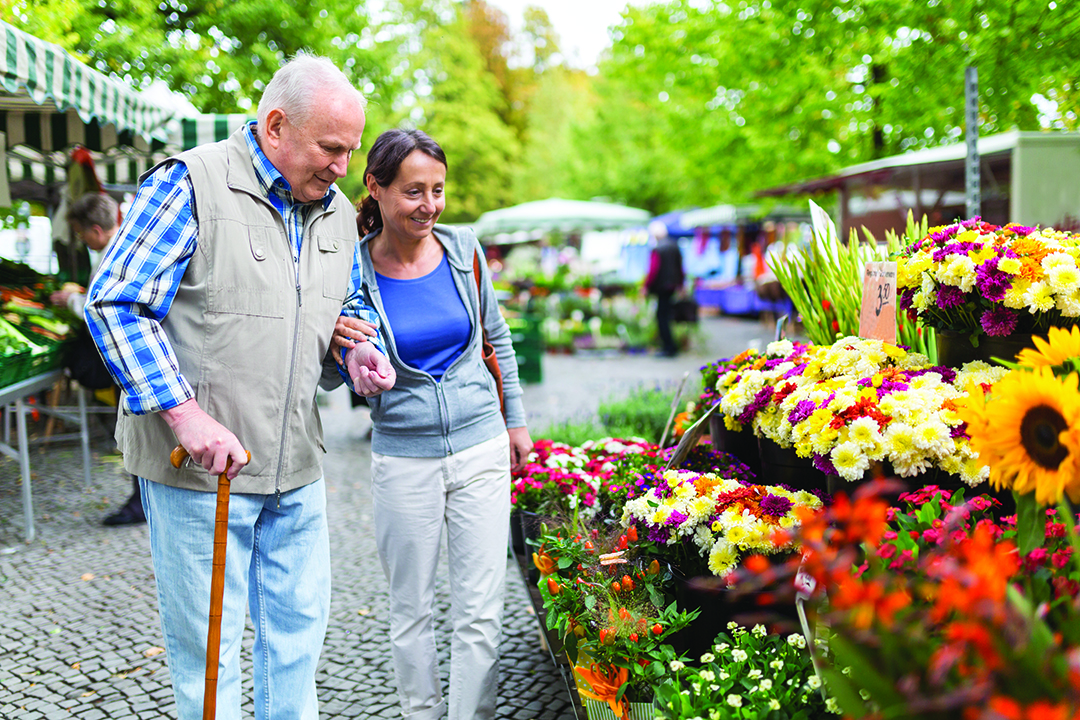 franchisee opportunity senior care provider and a client examine flowers at a market examining flowers