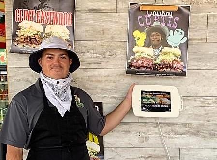 Employee Tucker Bascon directs customers to the Foodli Kiosk